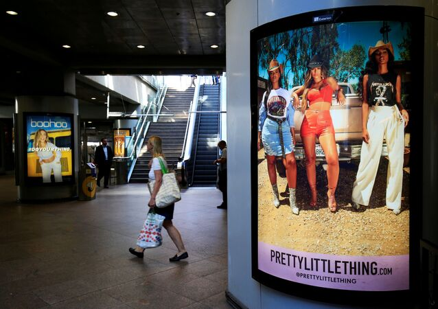 A shopper walks past an advertising billboards for Boohoo and for 'Pretty Little Things', a Boohoo brand, at Canary Wharf DLR station in central London, Britain, 17 September 2018