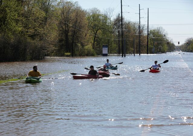 Residents paddle kayaks along a flooded street along the Tittabawassee River, after two dam failures submerged parts of Midland, Michigan, 20 May 2020