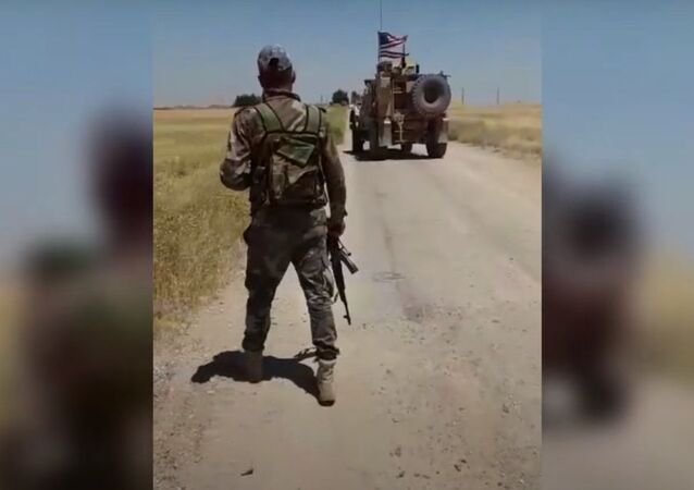 Syrian servicemen observe US armoured vehicles as they drive away after failing to breach a local checkpoint in al-Hasakah province.