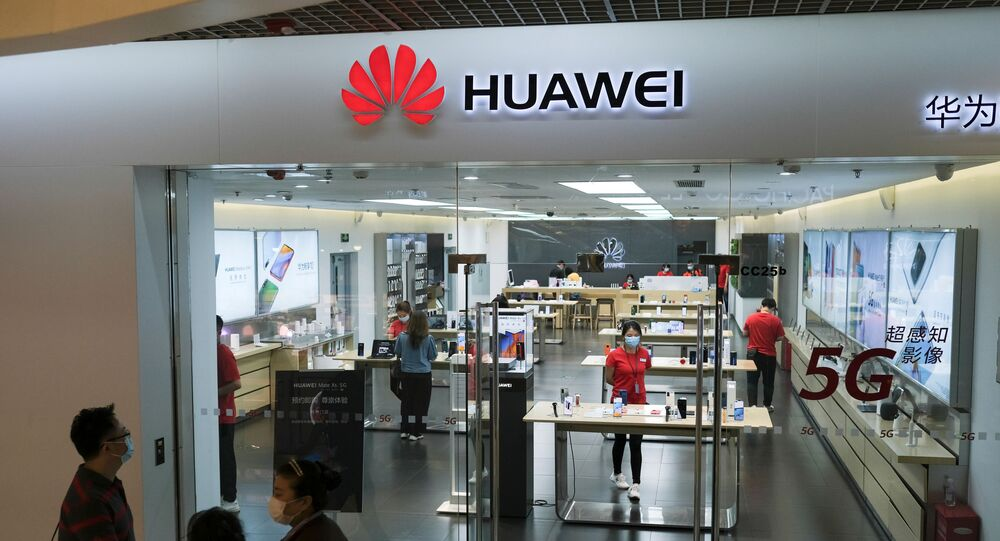 People wearing face masks walk past a?Huawei?store at a shopping mall, following an outbreak of the coronavirus disease (COVID-19), in Beijing, China May 18, 2020