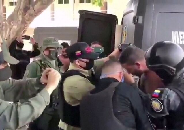Venezuelan soldiers wearing face masks surround a suspect moved from a helicopter after what Venezuelan authorities described was a mercenary incursion, at an unknown location in this still frame obtained from Venezuelan government TV video, May 4, 2020.