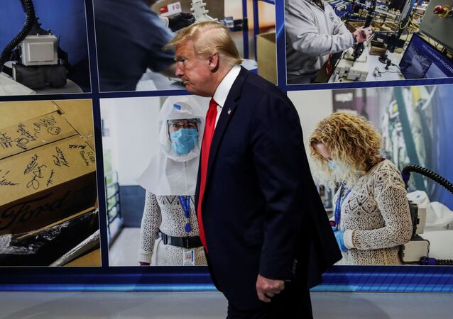 U.S. President Donald Trump walks past a display of photographs while touring the Ford Rawsonville Components Plant, which is making ventilators and medical supplies, during the coronavirus disease (COVID-19) pandemic in Ypsilanti, Michigan, U.S., May 21, 2020.