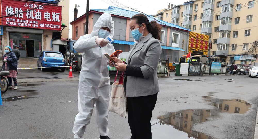 A worker in protective suit takes body temperature measurement of a woman following the coronavirus disease (COVID-19) outbreak in Jilin, Jilin province, China May 17, 2020. Picture taken May 17, 2020. cnsphoto via REUTERS   ATTENTION EDITORS - THIS IMAGE WAS PROVIDED BY A THIRD PARTY. CHINA OUT.