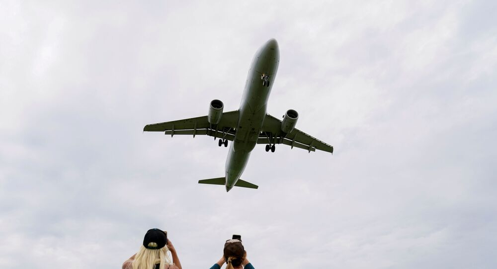 Flight attendants photograph a plane landing at Reagan National Airport during the coronavirus crisis while on a layover in Washington, U.S., April 29, 2020.