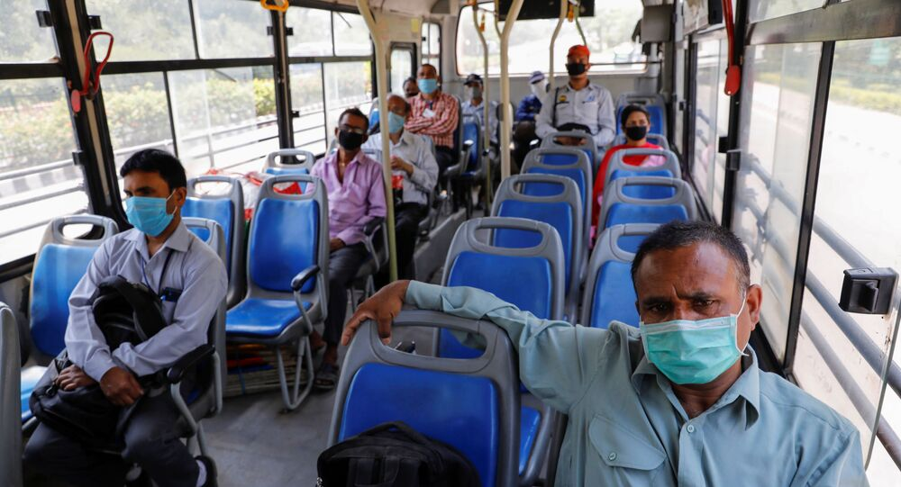 People wearing face masks travel in a bus, maintaining social distancing after few restrictions were lifted during an extended lockdown to slow the spread of the coronavirus disease (COVID-19) in New Delhi, India, May 20, 2020.