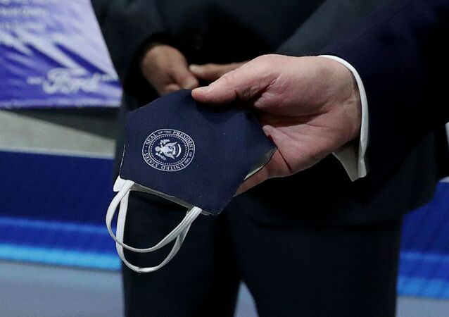 U.S. President Donald Trump holds a protective face mask with a presidential seal on it that he said he had been wearing earlier in his tour at the Ford Rawsonville Components Plant that is manufacturing ventilators, masks and other medical supplies during the coronavirus disease (COVID-19) pandemic in Ypsilanti, Michigan, U.S., May 21, 2020