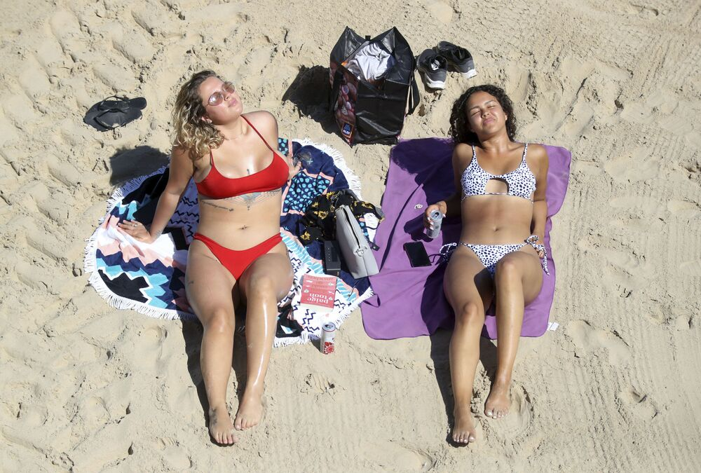 Sorrell Vince, 23, left, from Northampton and Bethany Heatley from Preston enjoying the sun on Cullercoats Beach,  in Tynemouth, England, Wednesday 20 May 2020. Lockdown restrictions due to the coronavirus outbreak have been relaxed allowing unlimited outdoor exercise and activities such as sunbathing. The Met Office has predicted the hottest day of the year so far with temperatures set to hit 28C (82.4F).