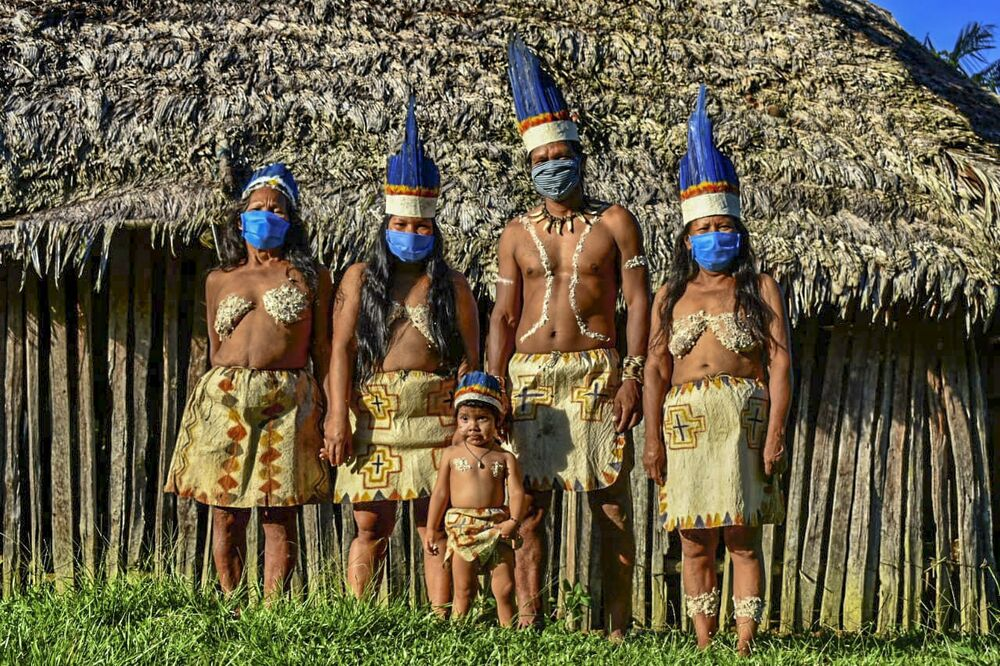 Colombian Huitoto indigenous people pose wearing face masks, amid concerns of the COVID-19 coronavirus, in Leticia, department of Amazonas, Colombia on 20 May 2020.