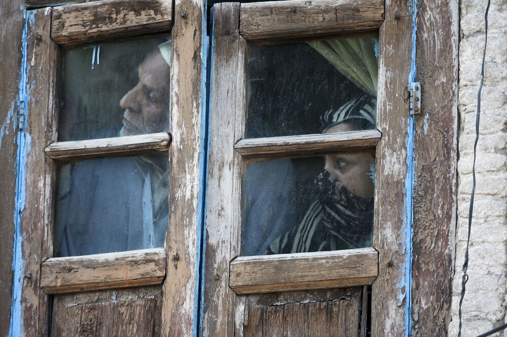 Residents watch out from their window in an area near the site of a gun battle between suspected militants and government forces in Srinagar on 19 May 2020. Two Kashmir militants including a key rebel leader were killed in a rare 12-hour gun battle in the main city Srinagar on May 19, officials said, sparking clashes between locals and police.