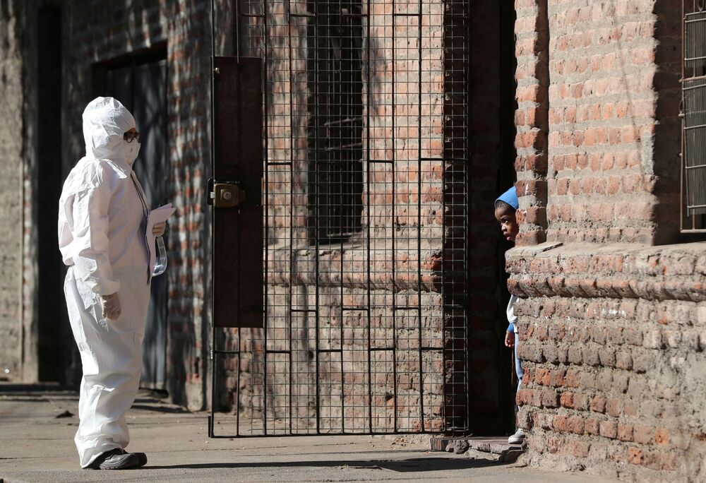 A woman wearing a protective suit talks to a child in a migrant neighbourhood during the start of a general quarantine to force down a surging rate of fresh coronavirus cases in the capital, amid the spread of the coronavirus disease (COVID-19) in Santiago, Chile 16 May 2020.