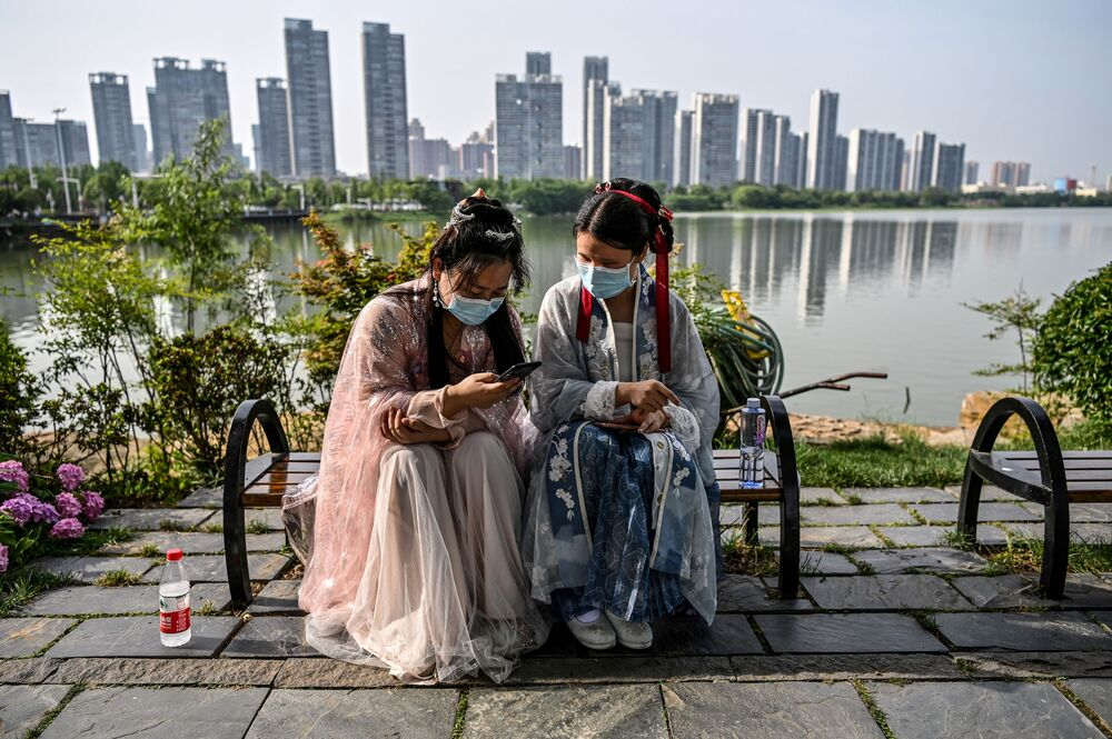 Young women wearing facemasks and traditional costumes of the Song dynasty and Tang dynasty are seated on a bench in a park next to the East Lake in Wuhan, in China's central Hubei province on 17 May 2020. Authorities in the pandemic ground zero of Wuhan have ordered mass COVID-19 testing for all 11 million residents after a new cluster of cases emerged over the weekend.