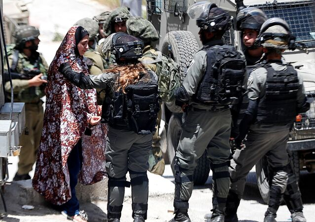 A Palestinian woman cries as she is stopped by Israeli forces after an Israeli soldier was killed by a rock thrown during an arrest raid, in Yabad near Jenin in the Israeli-occupied West Bank May 12, 2020