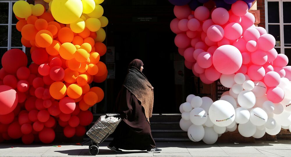 A muslim woman walks past balloons outside the National Hospital for Neurology and Neurosurgery, as the spread of the coronavirus disease (COVID-19) continues, in London, Britain, April 25, 2020