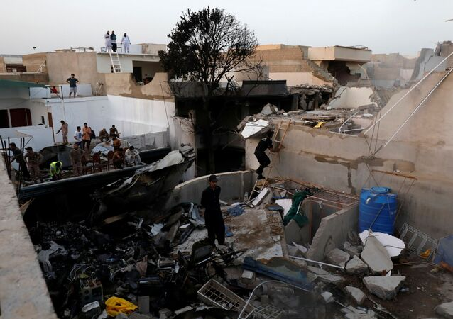 People stand on the roof of a house amidst debris from a passenger plane which crashed in a residential area near the airport in Karachi, Pakistan, 22 May 2020.
