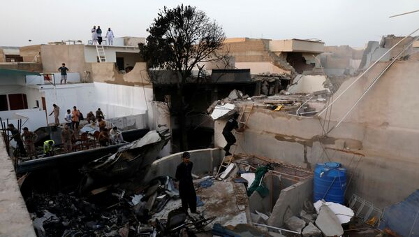 People stand on the roof of a house amidst debris from a passenger plane which crashed in a residential area near the airport in Karachi, Pakistan, 22 May 2020. - Sputnik International
