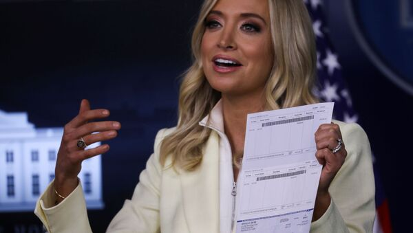 White House Press Secretary Kayleigh McEnany holds up a check signed by U.S. President Donald Trump for $100,000 made out to the Office of the Assistant Secretary for Health as she states that the president is donating his presidential salary to the Department of Health and Human Services, in the Brady Press Briefing Room at the White House in Washington, U.S., May 22, 2020 - Sputnik International