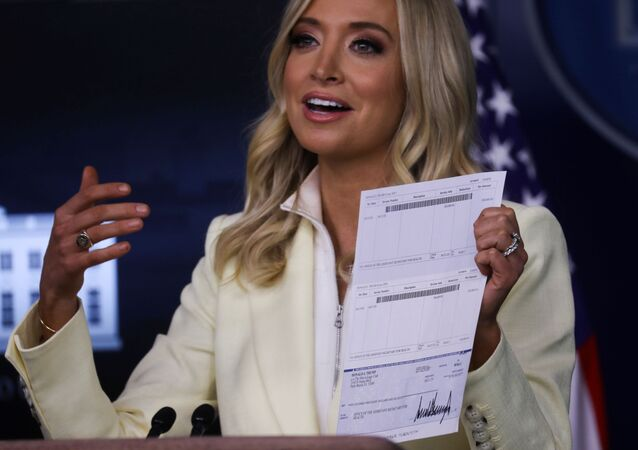White House Press Secretary Kayleigh McEnany holds up a check signed by U.S. President Donald Trump for $100,000 made out to the Office of the Assistant Secretary for Health as she states that the president is donating his presidential salary to the Department of Health and Human Services, in the Brady Press Briefing Room at the White House in Washington, U.S., May 22, 2020