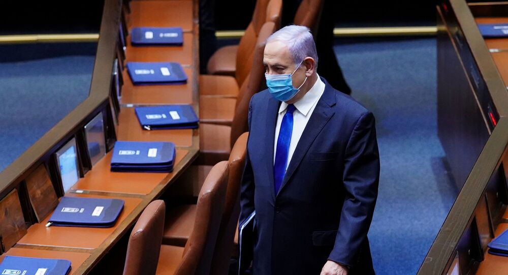 Israeli Prime Minister Benjamin Netanyahu wears a mask during a swearing in ceremony of his new unity government with election rival Benny Gantz, at the Knesset, Israel's parliament, in Jerusalem May 17, 2020.