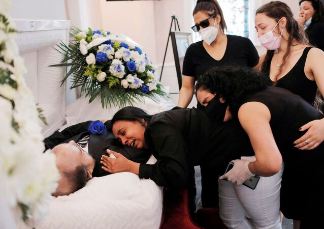 Maria Ortiz embraces the body of her partner Jose Holguin, 50, originally from the Dominican Republic and who died of complications related to the coronavirus disease (COVID-19), while she is supported by Mr. Holguin's family during his viewing service at International Funeral & Cremation Services in the Harlem neighborhood of Manhattan, New York City, U.S., May 16, 2020.