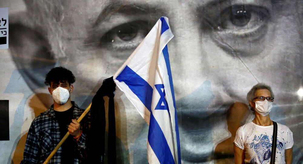 A man wearing a protective face mask holds an Israel's flag