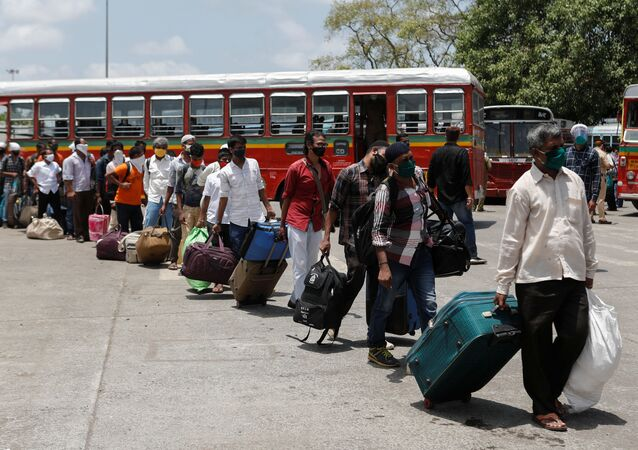 Migrants carrying luggage arrive at a railway station to board a train to their home state of Uttar Pradesh during an extended lockdown to slow the spread of the coronavirus
