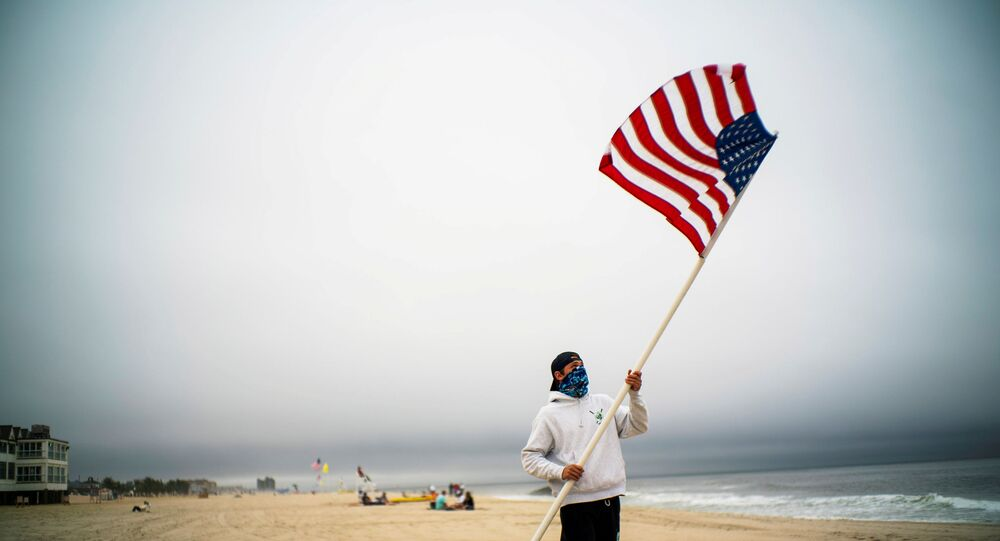 A beach guard removes the US flag of his spot