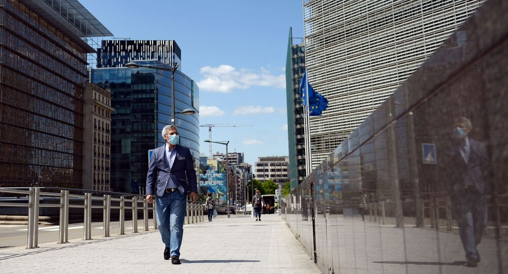 A man wearing a face mask walks past the European Commission headquarters as the spread of coronavirus disease (COVID-19) continues in Brussels, Belgium May 14, 2020