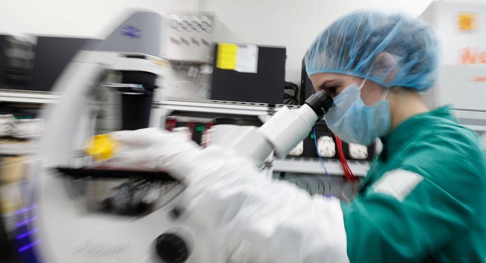 A scientist examines COVID-19 infected cells under a microscope during research for a vaccine against the coronavirus disease (COVID-19) at a laboratory of BIOCAD biotechnology company in Saint Petersburg, Russia May 20, 2020