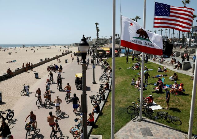 People sit at the beach as cyclists ride bicycles on Memorial Day weekend during the outbreak of the coronavirus disease (COVID-19) in Huntington Beach, California, U.S., May 23, 2020.