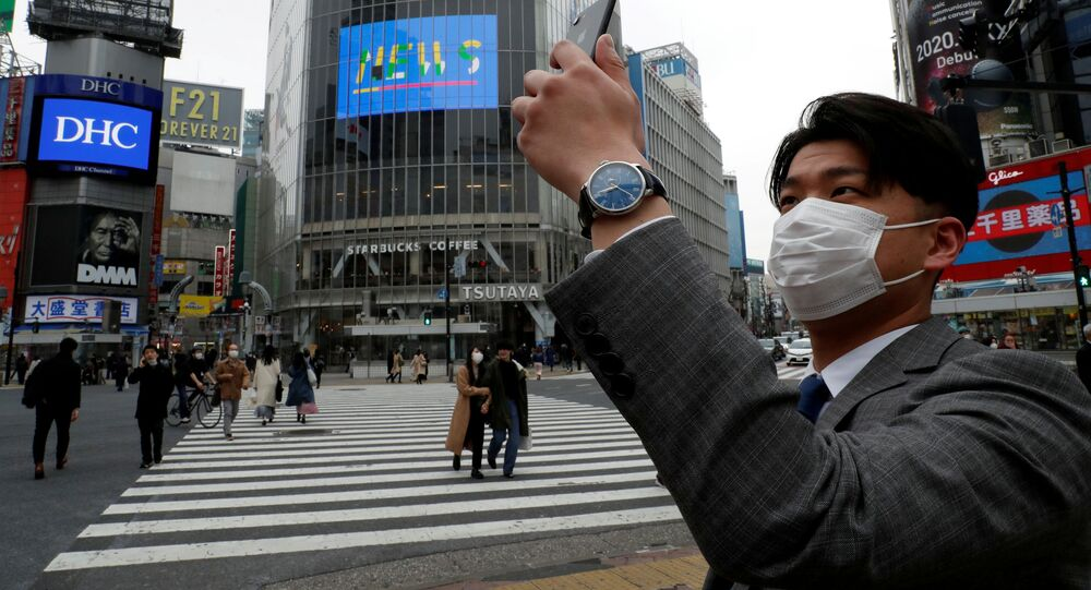 A man wearing a protective face mask, takes a photo with his mobile phone at noon, at Shibuya Crossing, during the coronavirus disease (COVID-19) outbreak, in Tokyo, Japan, March 31, 2020.