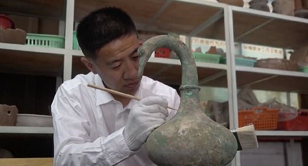 Researcher Yan Fei cleaning the swan-shaped Chinese ritual bronze unearthed in a tomb in Sanmenxia, Henan, China