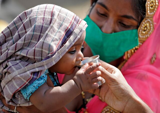 A child of a migrant worker drinks water as his mother holds him while waiting in a queue for transport to reach to a railway station to board a train to their home state of northern Uttar Pradesh, after a limited reopening of India's giant rail network following a nearly seven-week lockdown to slow the spreading of the coronavirus disease (COVID-19), in Ahmedabad, India, May 15, 2020