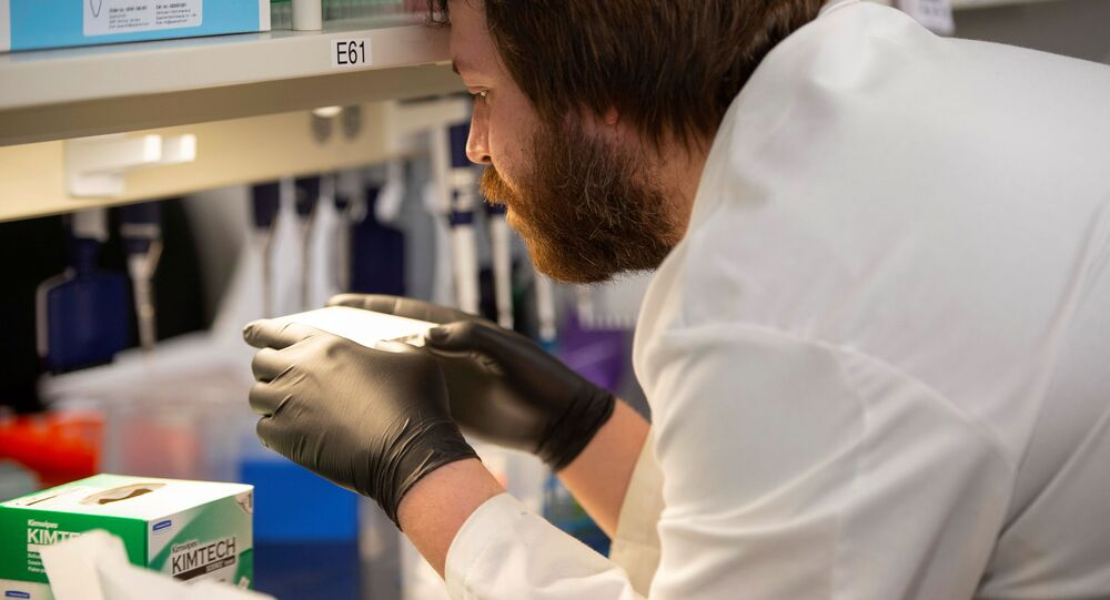 Researcher Cody Hoffmann checks the results of an automated liquid handler as researchers begin a trial to see whether malaria treatment hydroxychloroquine can prevent or reduce the severity of coronavirus disease (COVID-19) at the University of Minnesota in Minneapolis, Minnesota, U.S. March 19, 2020