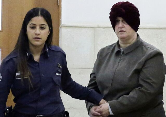 FILE - This Feb. 27, 2018 file photo, Australian Malka Leifer, right, is brought to a courtroom in Jerusalem. Leifer is wanted in Australia for 74 charges of sexual assault and the country's request for her extradition has been delayed for years