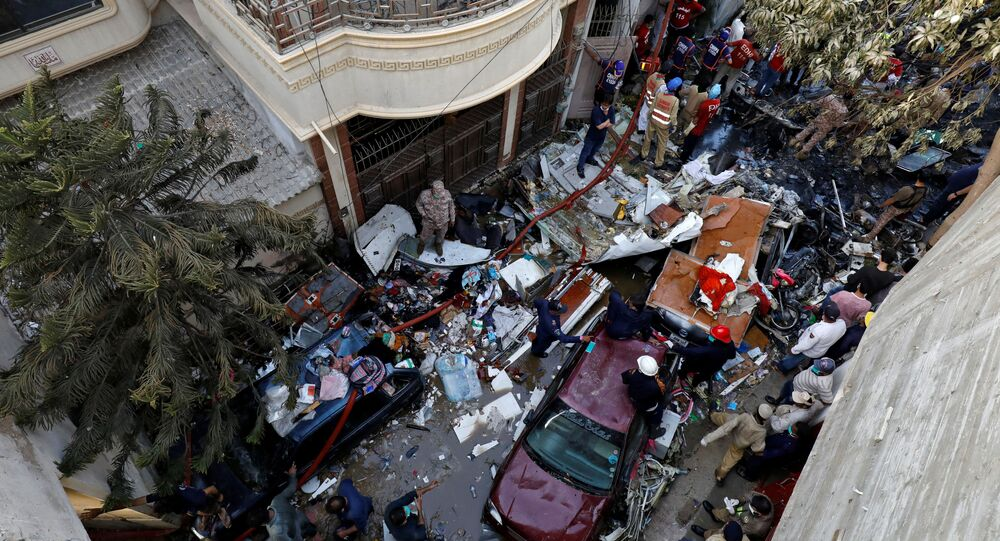 Rescue workers gather at the site of a passenger plane crash in a residential area near an airport in Karachi, Pakistan May 22, 2020.