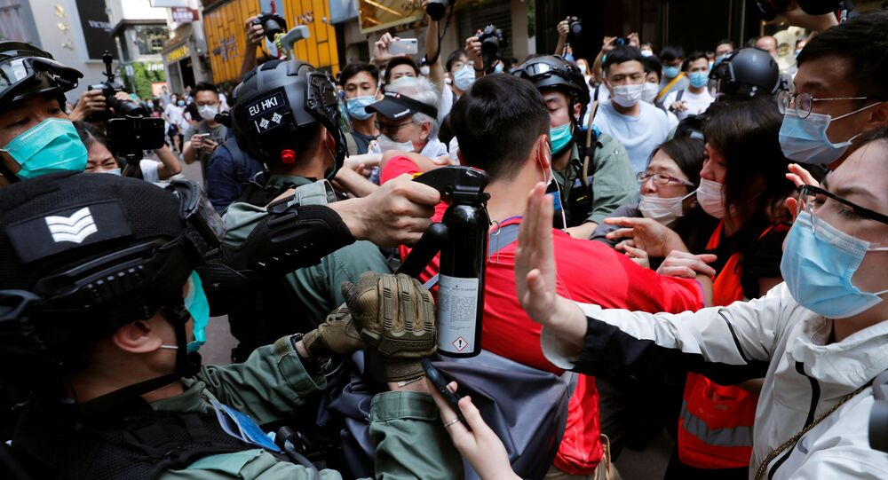 Anti-government demonstrators scuffle with riot police during a lunch time protest as a second reading of a controversial national anthem law takes place in Hong Kong, China May 27, 2020.