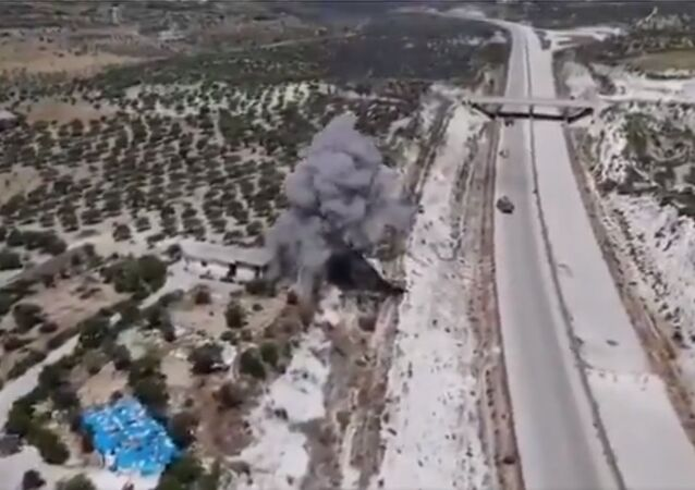 The moment of an explosion that occurred in a house or warehouse near the M4 road, west of Idlib, during the presence of vehicles and Turkish soldiers, what resulted in injuries among the elements
