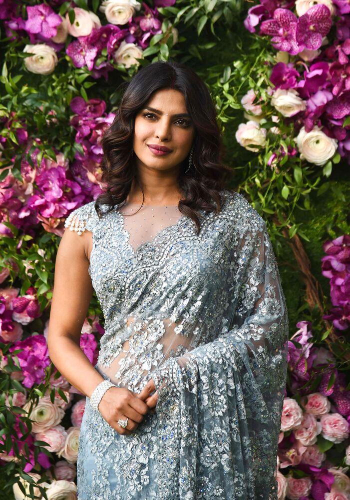 Bollywood actress Priyanka Chopra poses for photographs as she arrives to attend the wedding ceremony of Akash Ambani, son of Indian businessman Mukesh Ambani, in Mumbai on March 9, 2019.