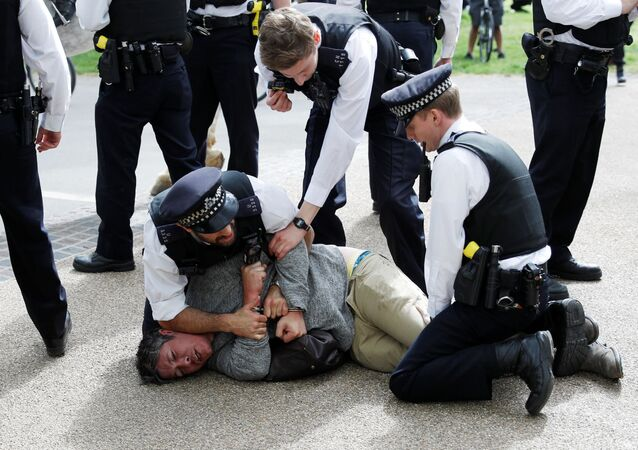 Police detain a protester in Hyde Park during COVID-19 lockdown