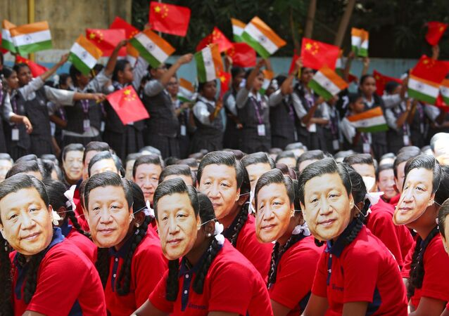 File photo of students wearing masks of China's President Xi Jinping as others wave national flags of India and China, ahead of the informal summit with India's Prime Minister Narendra Modi, at a school in Chennai, India, October 10, 2019