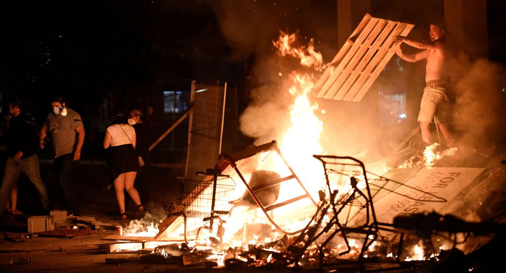 A protester adds wood to a fire barricade on 26th Ave S near the Minneapolis Police third precinct after a white police officer was caught on a bystander's video pressing his knee into the neck of African-American man George Floyd, who later died at a hospital, in Minneapolis, Minnesota, U.S. May 27, 2020. Picture taken May 27, 2020