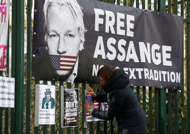 A supporter of WikiLeaks founder Julian Assange posts a sign on the Woolwich Crown Court fence, ahead of a previous hearing to decide whether Assange should be extradited to the United States, in London, Britain February 25, 2020.
