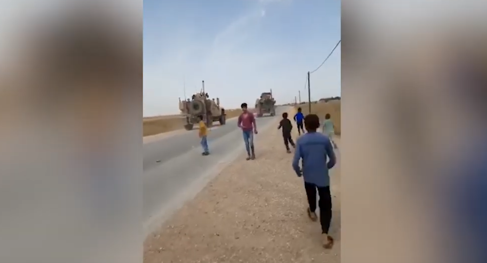 Syrian children running toward US military vehicles in al-Hasakah province, pelting them with rocks.