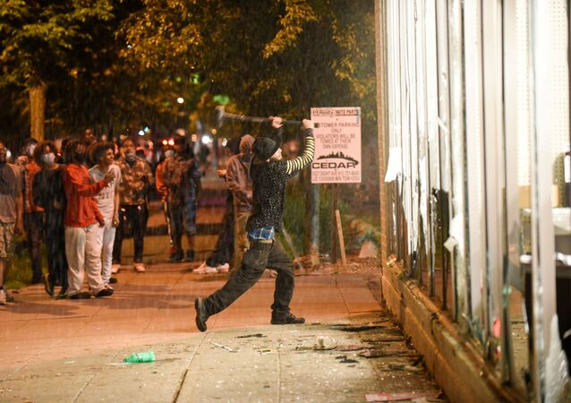 A protester vandalizes an O'Reilly's near the Minneapolis Police third precinct, where demonstrators gathered after a white police officer was caught on a bystander's video pressing his knee into the neck of African-American man George Floyd, who later died at a hospital, in Minneapolis, Minnesota, U.S. May 27, 2020.