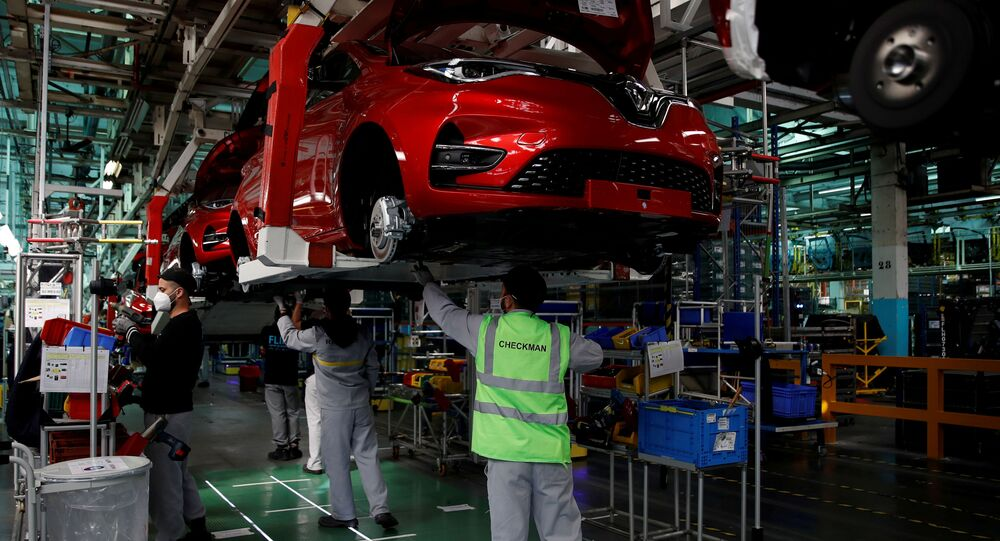Employees, wearing protective face masks, work on the automobile assembly line of Renault ZOE cars with sign on the floor to maintain social distancing at the Renault automobile factory in Flins as the French carmaker ramps up car production with new security and health measures during the outbreak of the coronavirus disease (COVID-19) in France, May 6, 2020