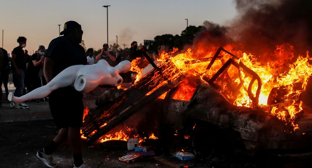 A man prepares to throw a mannequin onto a burning car at the parking lot of a Target store during protests after a white police officer was caught on a bystander's video pressing his knee into the neck of African-American man George Floyd, who later died at a hospital, in Minneapolis, Minnesota, U.S., May 28, 2020