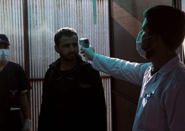A Syrian man has his temperature checked at the entrance of a quarantine centre, where those entering from Turkey are carefully monitored as a preventive measure against the spread of the coronavirus disease (COVID-19), in the town of Jisr al-Shughour in Idlib province, Syria, 30 April 2020