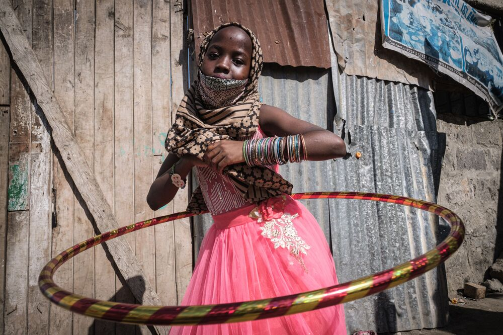 An orphan plays with her new hula hoop during a food and toy distribution, for approximately 500 orphans in 11 orphanages, launched by the National Muslim COVID-19 Response Committee to celebrate Eid al-Fitr, the Muslim holiday which marks the end of the fasting month of Ramadan at an orphanage in Nairobi, Kenya, on 25 May 2020.