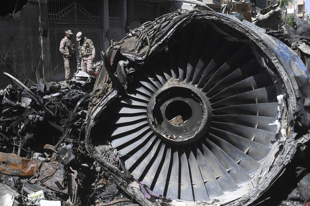 Security personnel stand beside the wreckage of the Pakistan International Airlines aircraft which crashed in a residential area days before, in Karachi on 24 May 2020. Ninety-seven people were killed in the 22 May crash and two survived.