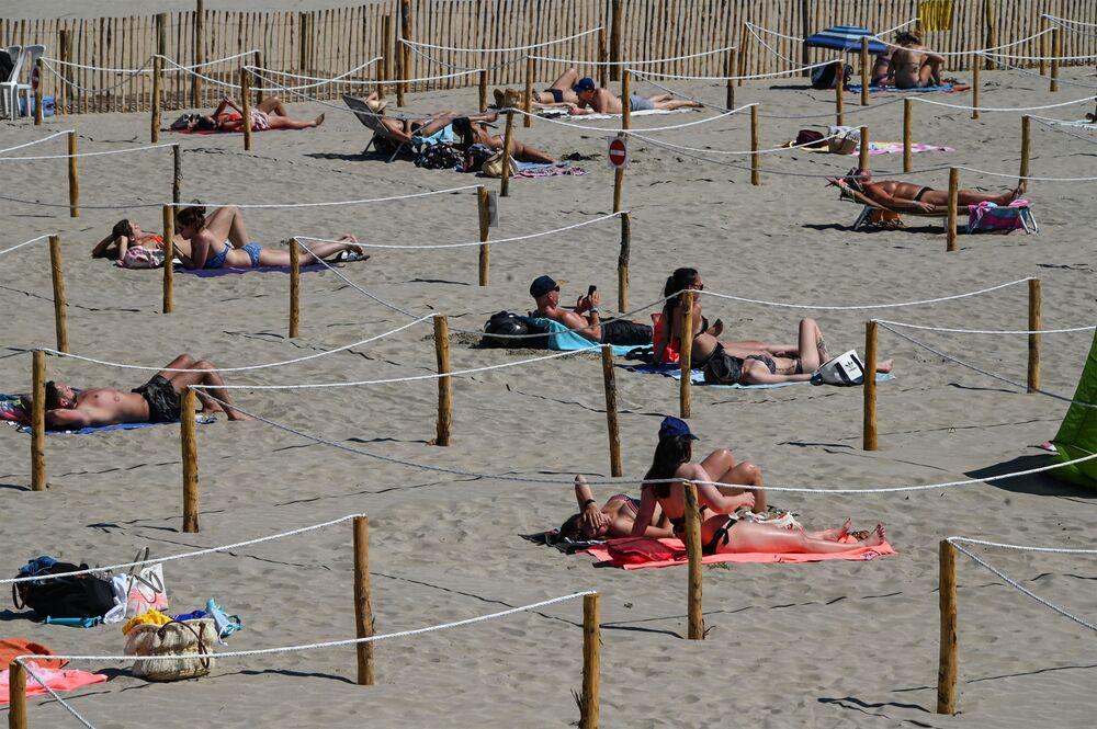 People sunbathe at Sunset Beach with separate areas to respect social distance in La Grande-Motte, in southern France on 26 May 2020, as the nation eases the lockdown measures taken to curb the spread of COVID-19 pandemic, caused by the new coronavirus.